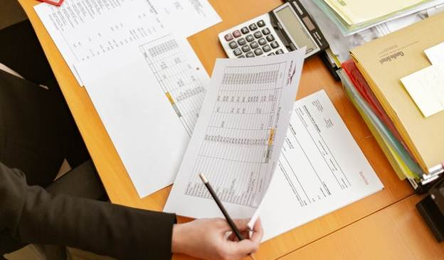 A person sitting at a desk, looking at company papers with numbers and statistics