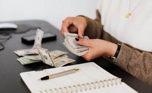 A person counting money, symbolizing ways to set up an emergency fund for your small business