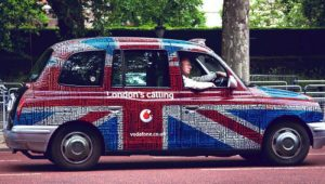 A car wrapped in Great Britain's flag and with an ad on it