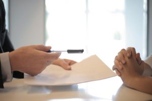 A man handing his potential renter a contract to sign and a pen