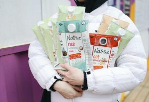 a woman recycling cartons of plant milk