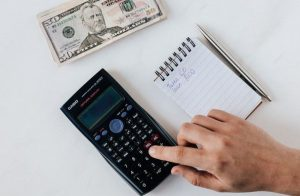 a man using a calculator to calculate extra income