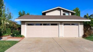 An exterior of a gray house with double garage doors